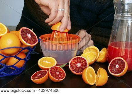 A Man Squeezes Orange Juice Into A Juicer From Tunisian Oranges. A Basket Of Oranges, Halved Oranges