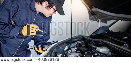 Asian Auto Mechanic Holding Digital Tablet Checking Car Engine Under Bonnet Hood In Auto Service Gar