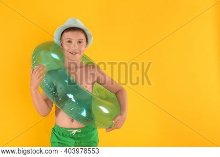 Cute Little Child In Beachwear With Bright Inflatable Ring On Yellow Background. Space For Text