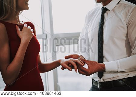 Man Is Proposing To Woman With Engagement Ring Near Window. A Man Puts A Ring On A Woman Who Has Bee