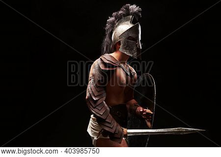 Gladiator With Sword And Armor On A Black Background. A Warrior In Gladiatorial Armor With A Chech A