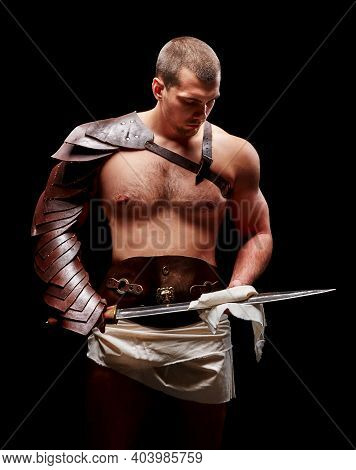 Gladiator With Sword And Armor On A Black Background. A Warrior In Gladiatorial Armor With A Sword I