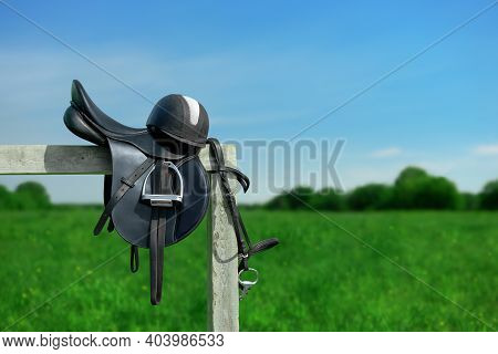 The Bridle, The Horse Saddle And The Riding Helmet Are On The Wooden Hitching Post In Outdoors.