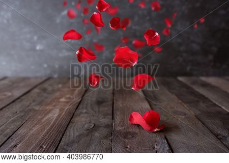 Red Rose Petals Float On Dark Wooden Vintage Background. Romantic Concept With Short Depth Of Field