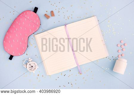 Pills, Sleeping Mask, Alarm Clock And Notepad On Blue Pastel Background. Concept Insomnia, Sleep Pro