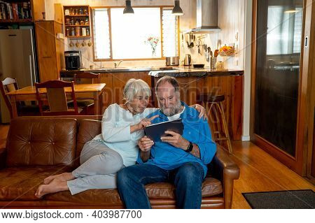 Happy Active Senior Man And Woman Video Calling Family Using Digital Tablet. Couple Enjoying Togethe