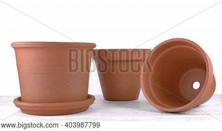 Group Of Terra Cotta Flower Pots Empty  On A Table On White Background
