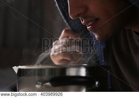 Man With Plaid Doing Inhalation Above Saucepot, Closeup