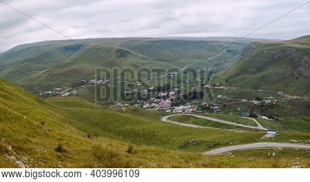 Beautiful mountain scenery. Mountains covered with green trees with residential settlements. In Kaba