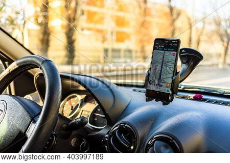 Using Waze Maps Application On Smartphone In Car Dashboard. Driver Using Maps App For Showing The Ri