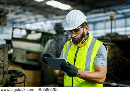 40's Male Industrial Engineer Wearing A White Helmet While Standing In A Heavy Industrial Factory Be