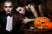 Portrait of a man and sexy woman vampires with halloween pumpkin against wooden background. Shot in a studio. poster