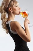 Beautiful girl drinking glass of water with golden fish and making wish poster