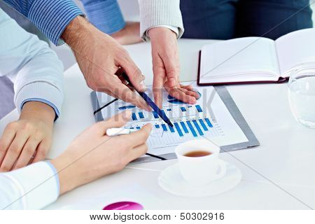 Image of human hands pointing at paper during explanation