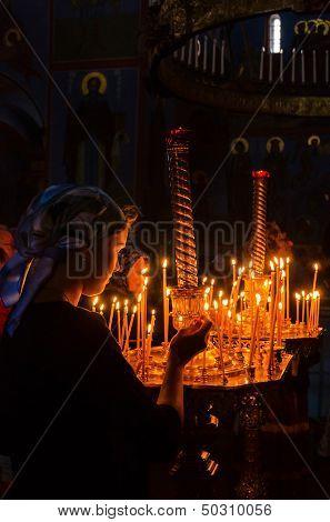 POCHAYIV, UKRAINE - AUGUST 14: Unidentified orthodox believer lights candles in Holy Dormition Pochayiv Lavra, Pochayiv, Ukraine on August 14, 2013