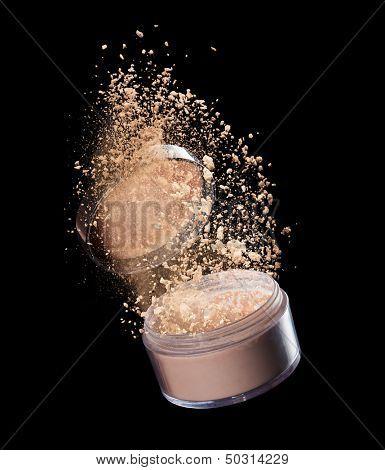 Isolated make-up powder explosion on black background