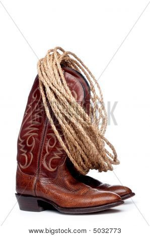 a vertical image of a pair of brown cowboy boots and a coil of rope on a white background poster