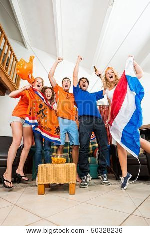 Dutch Sports fans cheer ecstatically over a goal and victory of the national team of the Netherlands at home, watching television with snacks and beer, dressed up in the national color, Orange