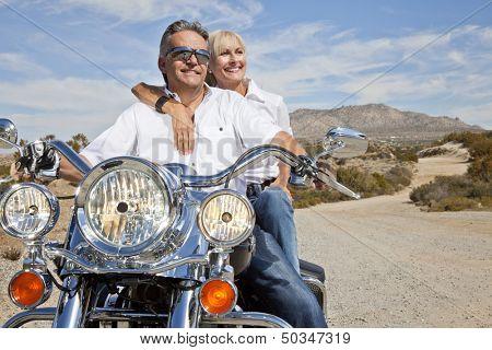 Senior couple on desert road sitting on motorcycle