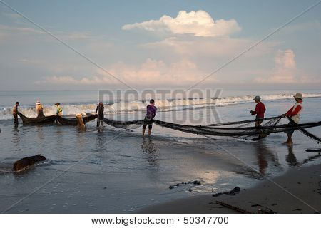 PADANG - AUGUST 25: Fishermen work as a team pull in the fishing nets from the sea in Padang, West Sumatera, Indonesia on August 25, 2013. Resources from the sea is a major revenue earner.