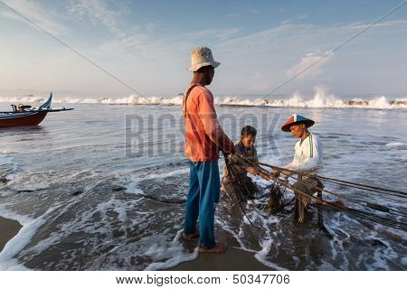 PADANG - AUGUST 25: Fishermen work as a team harvest the fish caught in the fishing nets in Padang, West Sumatera, Indonesia on August 25, 2013. Resources from the sea is a major revenue earner.