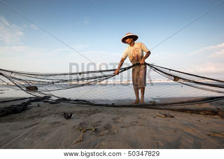 PADANG - AUGUST 25: A fisherman folds up the fishing nets in preparation for the next cast in Padang, West Sumatera, Indonesia on August 25, 2013. Resources from the sea is a major revenue earner.