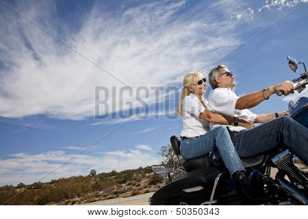 Senior couple riding motorcycle on desert road