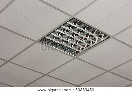 Fluorescent office ceiling lamp built-in on the white ceiling close-up view poster