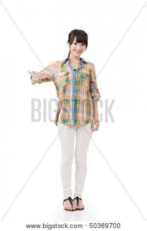 Asian woman puts hand on something imaginery. Full length portrait. Isolated on the white background.