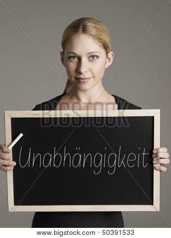 """Portrait of young businesswoman holding blackboard with German text """"Unabh_ngigkeit"""" (Independence)"""