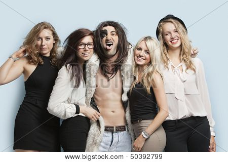 Portrait of playboy and happy women standing together against light blue background