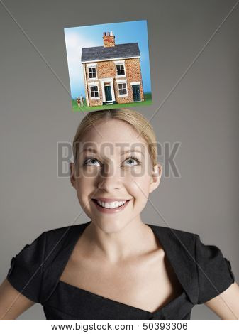 Model home on top of young woman's head representing homeownership
