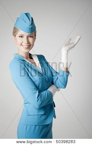 Charming Stewardess Dressed In Blue Uniform Pointing On Gray Background