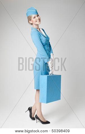 Charming Stewardess Dressed In Blue Uniform And Suitcase On Gray Background