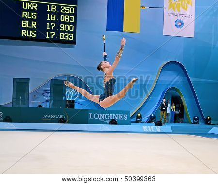 poster of KIEV - AUG 30: 32nd Rhythmic Gymnastics World Championships on August 30 2013 in Kiev Ukraine. 56 different nations representing all continents in the tournament. Gymnast take splits in the air.