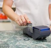 Close up of human hand putting credit card into payment machine in drug store poster