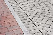 Brick paving types with pink sidewalk curb and drive made from plain interlocking concrete bricks poster