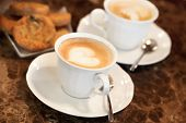 Two white cups of Cappuccino coffee with heart shaped milk foam. Selective focus poster