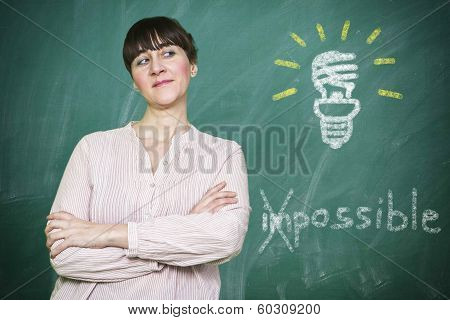 Woman Smiles Writes On A Blackboard The Concept Of Saving Energy Is Possible