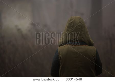 strange person walking in a dark foggy forest