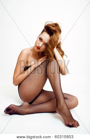 Sexy young woman in black pantyhose and lingerie, red lips, sexy look poster