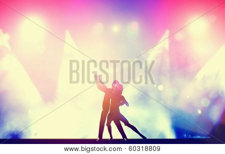 A couple of dancers in elegant, passionate dancing pose in club lights. Party, nightlife. Vintage, retro style