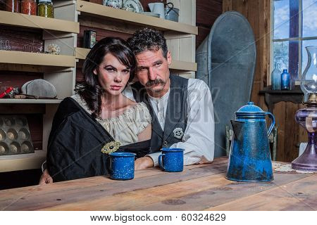 Serious looking western sheriff and woman pose inside of a house poster