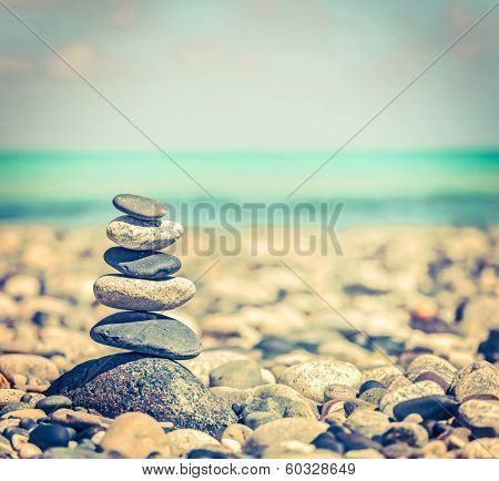 Vintage retro hipster style travel image of Zen meditation background -  balanced stones stack close up on sea beach