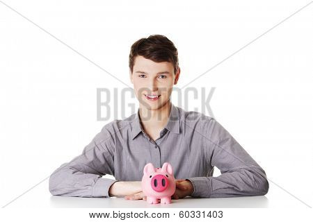 Young man sitting behind the desk with piggy bank on white