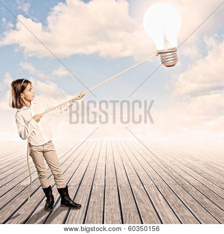 little girl holding a light bulb with a rope on a wharf