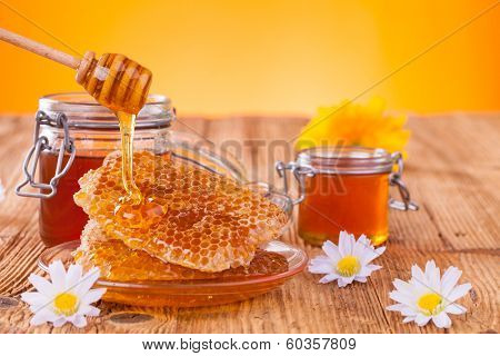 Honey in jar with honeycomb and wooden drizzler poster