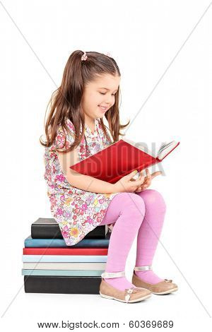 Female child reading a story seated on stack of books isolated on white background