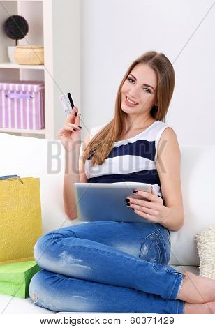Young woman sitting with tablet on sofa and holding credit card in her hand, at home