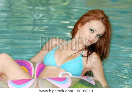 Sexy Brunette Woman Floating In Swimming Pool